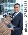 Smiling businessman using laptop in the office 27429453