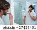 Man looking in mirror while brushing her teeth in bathroom 27429461