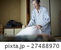 一人暮らしをする高齢者 寝具を畳む男性 27488970