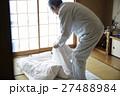 一人暮らしをする高齢者 寝具を畳む男性 27488984