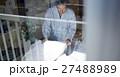 一人暮らしをする高齢者 寝具を畳む男性 27488989