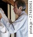 一人暮らしをする高齢者 寝具を畳む男性 27489061