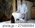 一人暮らしをする高齢者 寝具を畳む男性 27489064