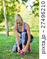 Female jogger tying laces on her shoes outside 27496210