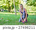 Female jogger tying laces on her shoes outside 27496211