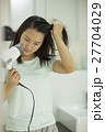 ドライヤーで髪を乾かす若い女性 27704029