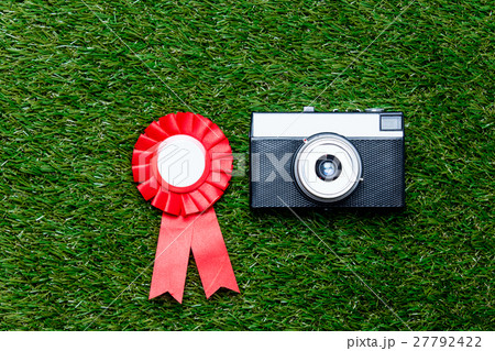 Red reward and vintage camera on green grass background 27792422