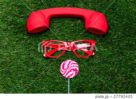styled red glasses with lollipop and handset on green grass backの写真素材 [27792435] - PIXTA