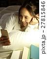 布団の中でスマホを見る女の子 27815846