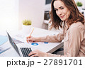 Cheerful young businesswoman working in the office 27891701