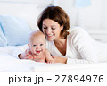 Baby and mother at home in bed. Mom and child. 27894976