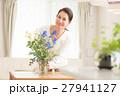 リビングで美しい花を活ける中年女性 27941127