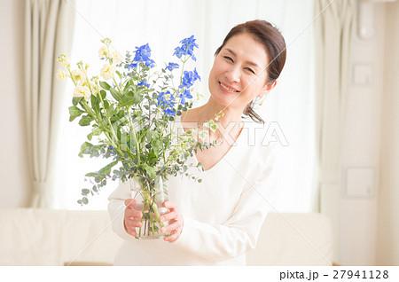リビングで美しい花を活ける中年女性 27941128