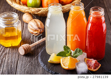 Fresh citrus juices on a dark wooden background. 27981139