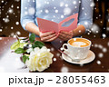 woman with coffee and flower reading greeting card 28055463