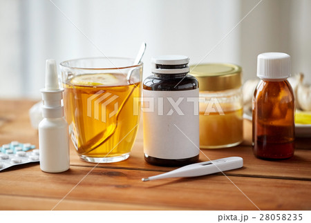 drugs, thermometer, honey and cup of tea on woodの写真素材 [28058235] - PIXTA