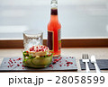 salad, bottle of drink, glass and cutlery on table 28058599
