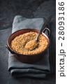 Grain bulgur in a copper bowl and metal spoon 28093186