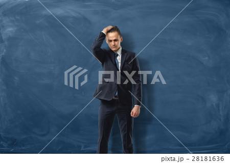 businessman on blue chalkboard background holdingの写真素材