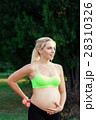 Smiling pregnant woman caress her belly at nature 28310326