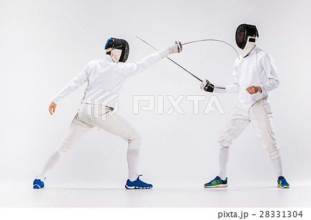 The two men wearing fencing suit practicing with 28331304