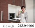 キッチンに立ち電子レンジを使う女性 28394400