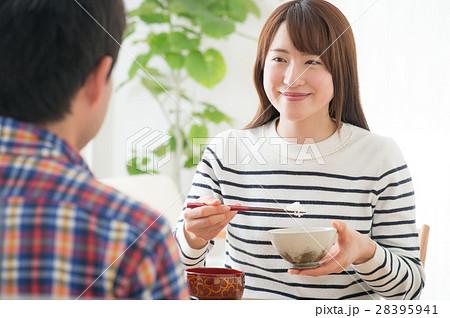 食卓で向かい合い朝ごはんを食べる若夫婦 28395941