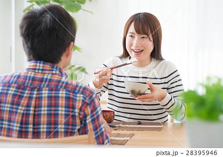食卓で向かい合い朝ごはんを食べる若夫婦 28395946