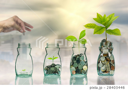 Hand putting mix coins and seed in clear bottle on cityscape photo blurred cityscape background,Business investment growth conceptの写真素材 [28403446] - PIXTA