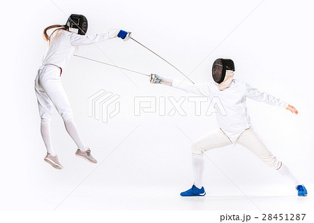 The woman and man wearing fencing suit practicing 28451287