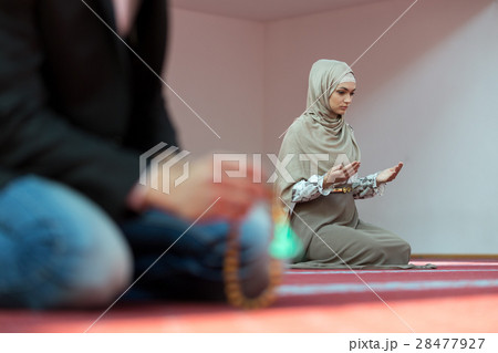 Muslim man and woman praying in mosque 28477927