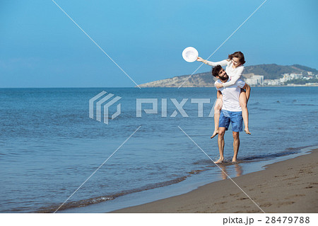 A guy carrying a girl on his back, at the beach 28479788