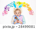 Child on Easter egg hunt. Pastel rainbow eggs. 28499081