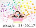 Child on Easter egg hunt. Pastel rainbow eggs. 28499117