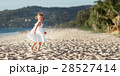 Happy child girl running on beach by sea in summer 28527414