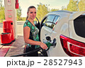 Young woman-motorist fills her car with benzine 28527943
