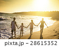 happy young family walking on beach at sunset 28615352