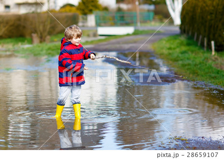 Little kid boy playing with fishing rod by puddle for Little kid fishing pole