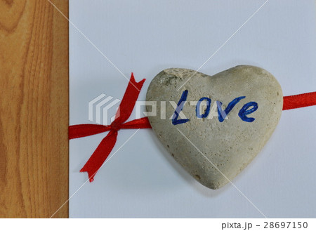 heart rock on white paper tie red ribbonの写真素材 [28697150] - PIXTA