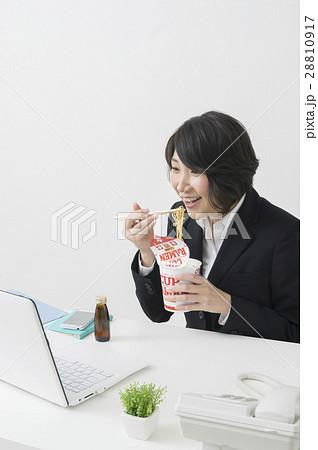 仕事中にカップラーメンを食べるビジネスウーマン 28810917