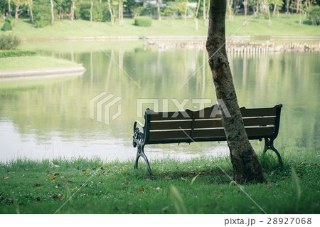 Empty wooden bench at lake green park. 28927068