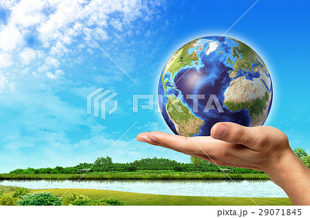 Man hand with earth globe on it and a beautiful green landscape with river and blue sky, on background. 29071845