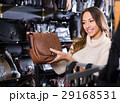 Young friendly woman buying leather purse in shop 29168531