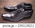 木のテーブルの上の横向きの黒い革靴 29313621