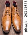 木のテーブルの上の正面向きの茶色のデザートブーツ 29313623