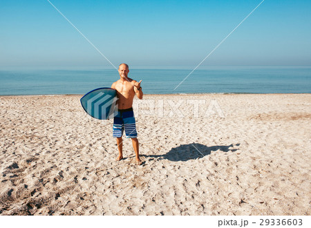 Surfer is going to surf in the ocean in a sunny 29336603