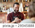 man or waiter serving customer at bar 29345888