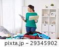 woman packing travel bag at home or hotel room 29345902