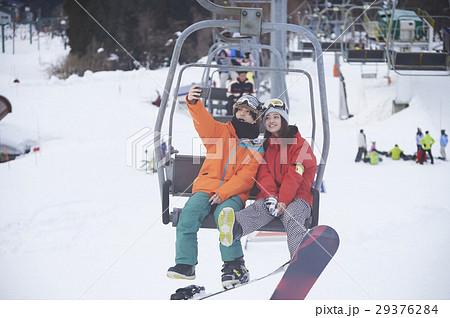 スキー場 リフトに乗るカップル スマホ 撮影 29376284