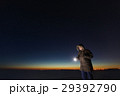 Silhouette of a man with a flashlight, observing 29392790